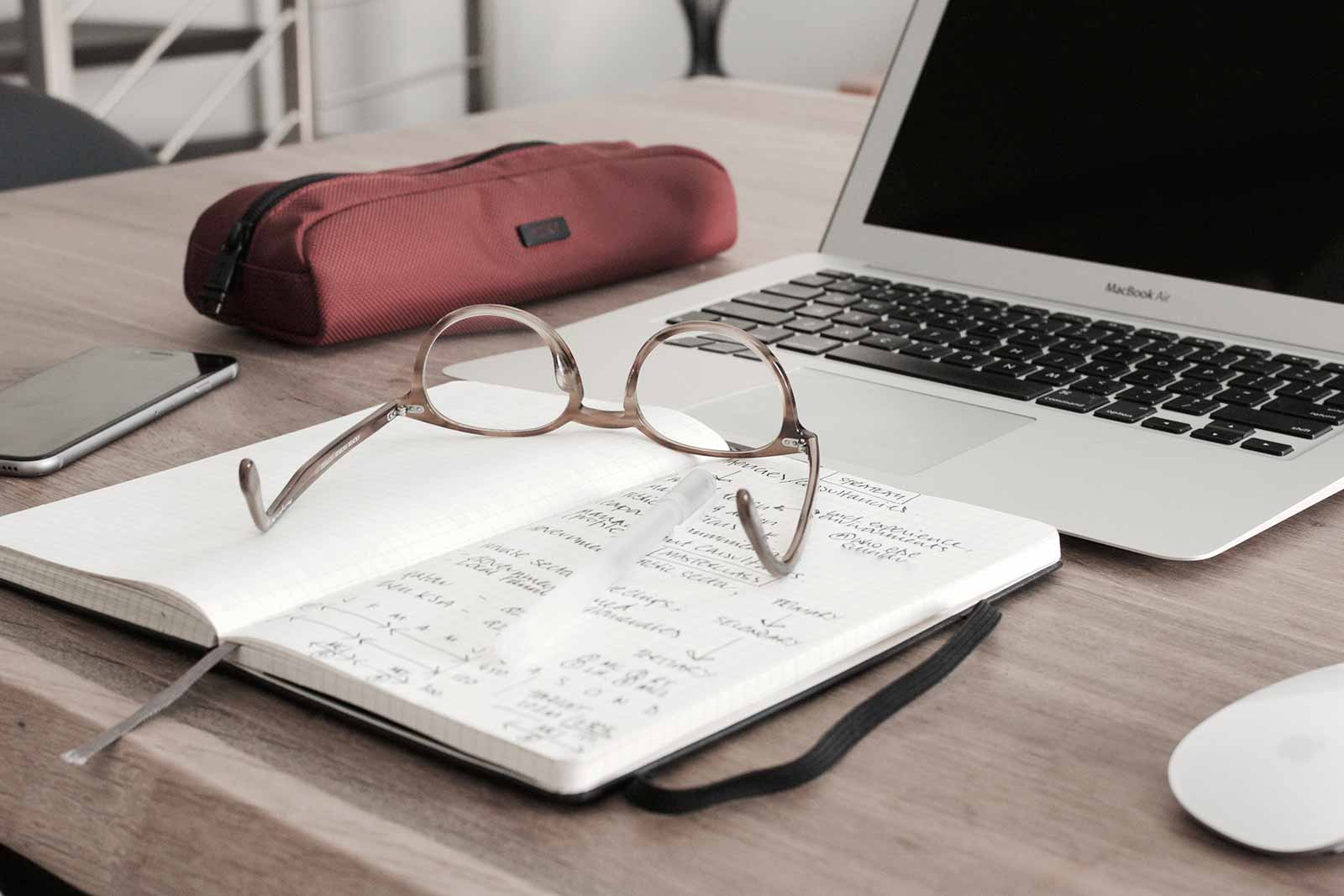 Notebook opened with glasses and a laptop