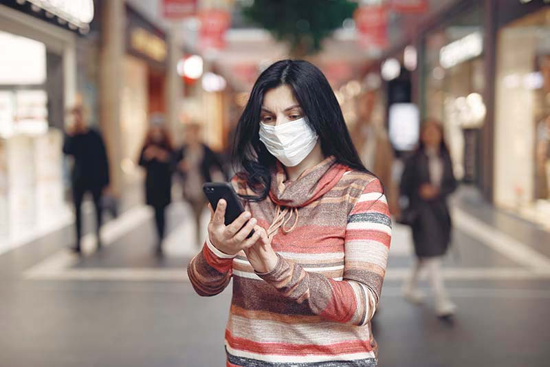 Lady holding a cell phone and wearing a mask